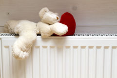 Teddy bear rying radiator Royalty Free Stock Photo