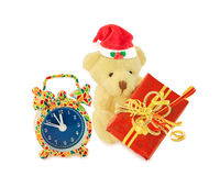 Teddy bear Santa with gift and alarm clock on white. Stock Image
