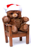 Teddy Bear With Santa Hat in Chair Stock Photos