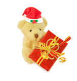 Teddy bear with Santa hat and gift on white. Stock Photos