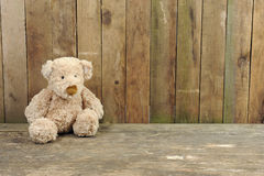 Teddy bear seated against a wooden wall Royalty Free Stock Images