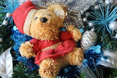 Teddy bear, silvery Christmas balls and blue tinsel on a Christmas wreath Royalty Free Stock Photos