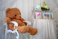 Teddy bear sit on the chair. Teddy bear sit on the chair and picture frames on the table Stock Images