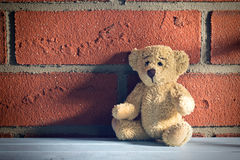 Teddy bear sit in front of a brick wall Stock Photography