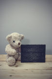 Teddy bear sit on wooden floors. Teddy bear sit on wooden floors have blackboard. Vintage style Stock Image