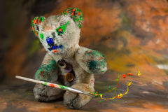 Teddy bear sits and make magic with bursting paint Stock Photo