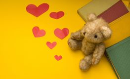 A teddy bear sits near books on a yellow background of scattered hearts stock photo