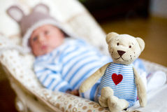 The teddy bear sitting on the baby cradle Royalty Free Stock Photography