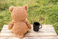 Teddy bear sitting backwards and coffee cup on wooden table. Royalty Free Stock Photography