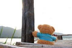 Teddy Bear sitting on bamboo bridge near the lake for waiting so Stock Photography