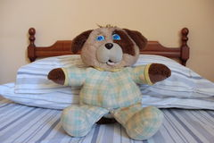 Teddy bear sitting on bed Royalty Free Stock Image