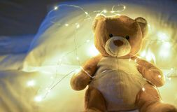 Teddy bear sitting on the bed with little light bulb, defocus,copy space stock photography