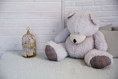 Teddy bear sitting on a bed next to a caged little bear Stock Photos
