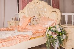 Teddy bear sitting on big bed in cozy and light bedroom.big soft toy bear sits on bed in pastel colors. Luxury home royalty free stock photography