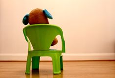 Teddy bear sitting on a chair looking at blank white wall stock photos