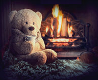 A teddy bear is sitting by the fireplace with a cup Royalty Free Stock Photo