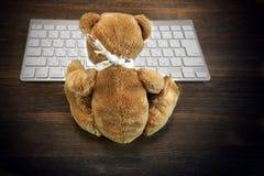 Teddy Bear Sitting In Front del teclado de la PC fotos de archivo