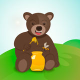 Teddy bear sitting on the grass and eating honey. Stock Image