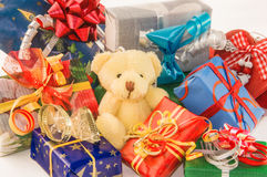 Teddy bear sitting with heap of gift boxes. Royalty Free Stock Photo