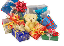 Teddy bear sitting with heap of gift boxes on white. Royalty Free Stock Photos