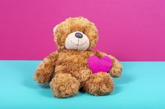 Teddy bear with felt heart on two color background stock image