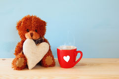teddy bear sitting and holding a heart next to cup of coffee Royalty Free Stock Photography