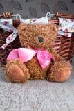 Teddy Bear sitting near wicker basket Royalty Free Stock Photo