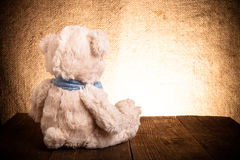 Teddy bear is sitting on the old wooden table Royalty Free Stock Images