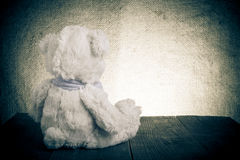 Teddy bear is sitting on the old wooden table. Toned Stock Photos