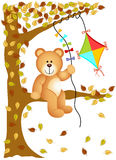 Teddy bear sitting on the tree with kite wind Royalty Free Stock Images