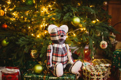 Teddy bear sitting under decorated with lights Christmas tree with gift boxes Stock Photography