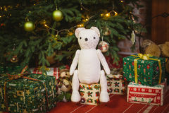 Teddy bear sitting under decorated with lights Christmas tree with gift boxes Stock Photo