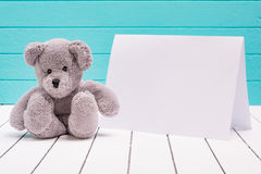 Teddy bear sitting on white wooden floor in blue-green background with blank note Royalty Free Stock Photography