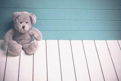 Teddy bear sitting on white wooden floor with blue-green background lonely Royalty Free Stock Photos