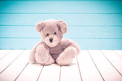 Teddy bear sitting on white wooden floor with blue-green background lonely Stock Images