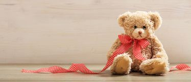 Teddy bear on a wooden floor royalty free stock image