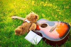 Teddy bear sleep on classical guitar on field. Royalty Free Stock Photos