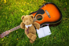 teddy bear on classical guitar on field stock photo. Black Bedroom Furniture Sets. Home Design Ideas