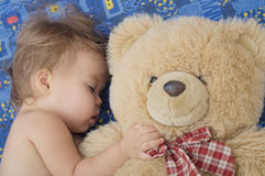 Teddy bear and sleeping cute baby Royalty Free Stock Image