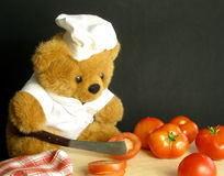 Teddy bear is slicing tomatoes. Don't cut your fingers Teebee royalty free stock images