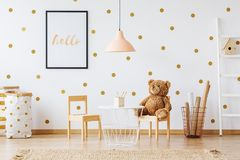 Teddy bear on small chair. Teddy bear sitting on a small chair in cute kids playing room Royalty Free Stock Photography