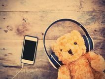 Teddy bear with smiling happy face in headphone and mobilephone. Teddy bear with smiling happy face in headphone and mobile phone lay down on wooden background Stock Photo