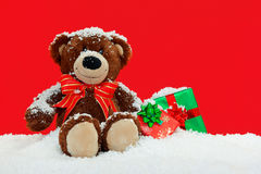 Teddy bear in the snow with gifts. A handmade teddy bear sitting in the snow with gift wrapped Christmas presents against a red background Royalty Free Stock Photo