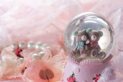 Teddy bear in snow globe decoration on pink fabric background. Royalty Free Stock Image