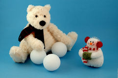 Teddy bear with snowman and snowballs. Polar bear toy with little snowman and styrofoam snowballs on blue background Stock Photography