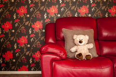 Teddy Bear Soft Toy på rött läder Sofa Stylish Lifetsyle Arkivbild