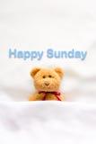 Teddy Bear som ligger i den vita sängen med meddelandet & x22; Lyckliga Sunday& x22; Arkivfoto
