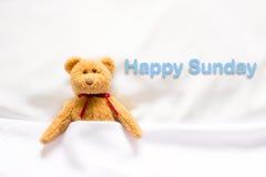 Teddy Bear som ligger i den vita sängen med meddelandet & x22; Lyckliga Sunday& x22; Royaltyfri Fotografi