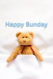 Teddy Bear som ligger i den vita sängen med meddelandet & x22; Lyckliga Sunday& x22; Arkivbild