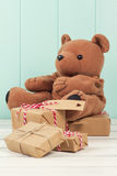Teddy bear and some gifts. Teddy bear and some paper parcels wrapped tied with tags. Christmas gift boxes on a white wooden table. Vintage Style royalty free stock images